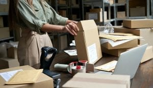 Female small business owner packing ecommerce order package in box at table.