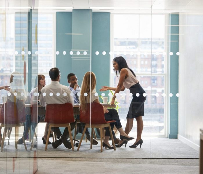 Female boss stands leaning on table at business meeting